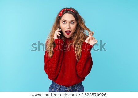 Image of young nice woman talking on smartphone and expressing surprise Stock photo © deandrobot