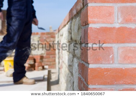 Stonemason holding up a trowel Stock photo © photography33