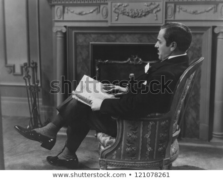 Man with newspaper sitting in vintage armchair Stock photo © Massonforstock