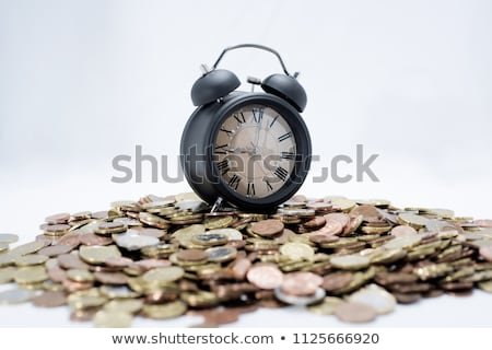 Stock photo: TIME IS MONEY concept: alarm clock and lots of euro coins