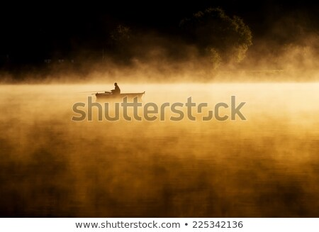 early morning sunrise boating on the lake in a huge fog stock photo © geribody