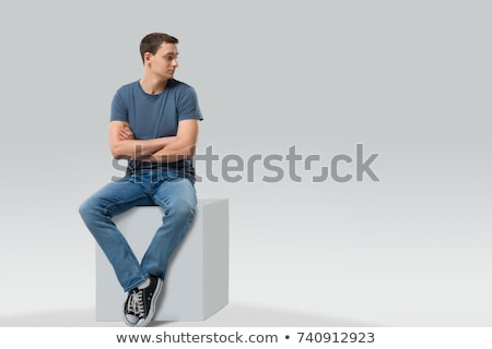 young casual man sitting on studio background stock photo © feedough