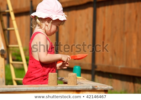The girl plays to a sandbox.