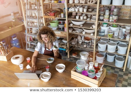 Beautiful woman artist using laptop in workshop Stock photo © deandrobot