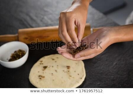 Woman adding dry fruits over flattened dough Stock photo © wavebreak_media
