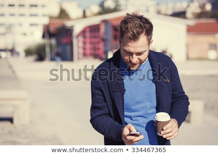 Stock photo: Man text messaging at table