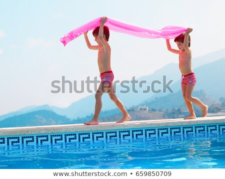 Two brothers carrying inflatable by pool Stock photo © IS2