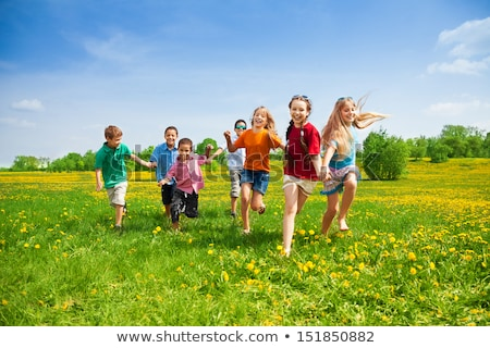 group of kids running in a field stock photo © is2