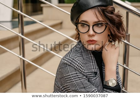 Young brunette girl in black glasses. Cat glasses. The hair is gathered in a bun. The girl points a  Stock photo © Traimak