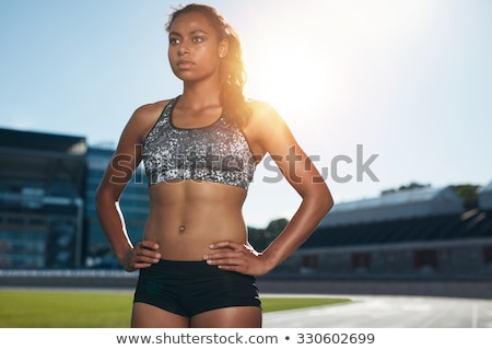 Confident young sportswoman standing outdoors Stock photo © deandrobot