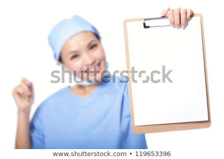 Young beautiful female doctor showing on clipboard with pen on white background Stock photo © Traimak