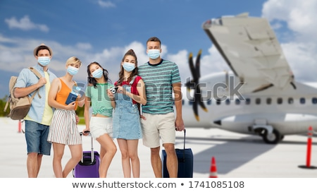 friends with backpacks over plane on airfield Stock photo © dolgachov