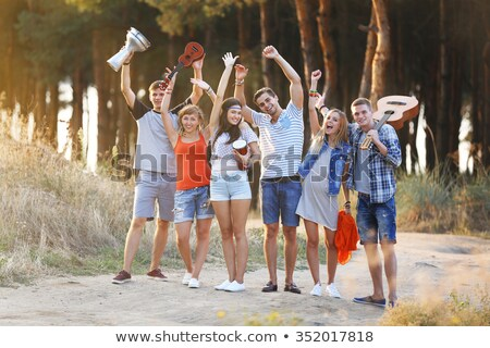 Group of young hippies men and women having fun, and playing gui Stock photo © deandrobot