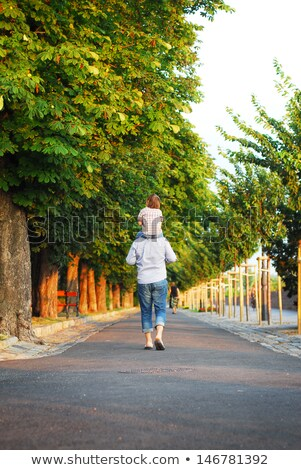 father carrying son with autumn leaves in city stock photo © dolgachov