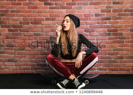 Photo of european sporty girl 20s, sitting on skateboard with ci Stock photo © deandrobot