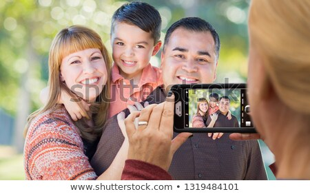 Woman Taking Pictures of A Mixed Race Family with Her Smart Phon Stock photo © feverpitch