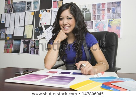 Young confident fashion designer looking at sketch on paper during work Stock photo © pressmaster