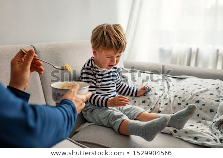 A cute baby who cry on the hand of is father Stock photo © Lopolo