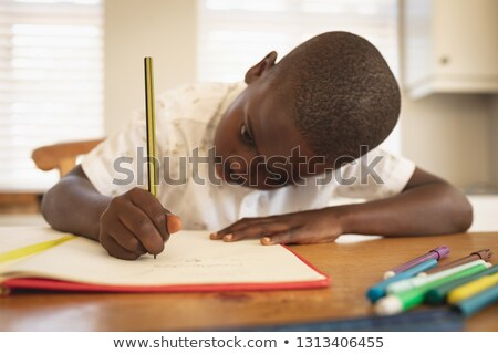 Close-up African American boy doing homework on dining table in kitchen at home Stock photo © wavebreak_media