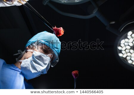 Low angle view of a mature Caucasian female surgeon holding surgical instruments before starting the Stock photo © wavebreak_media