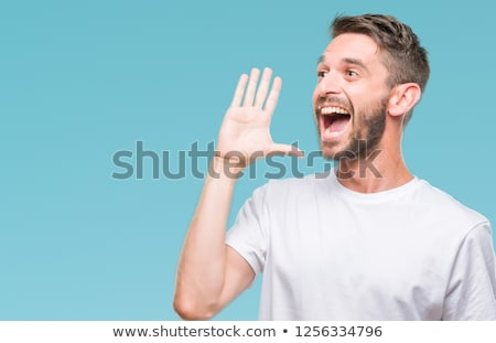Young handsome man shouting and screaming loud to side with hand on mouth and copy space for text Stock photo © GVS