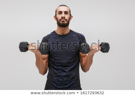 Image of young brunette sportsman wearing tracksuit lifting dumb Stock photo © deandrobot