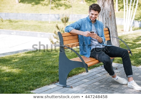 Young man text messaging in park  Stock photo © dacasdo