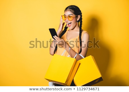 Happy young shopaholic carrying her bags Stock photo © stryjek