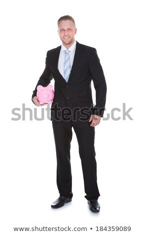 Stylish businessman in a suit standing holding a piggy bank Stock photo © AndreyPopov