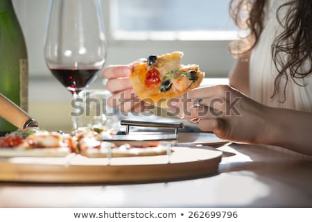 woman eating homemade pizza and drinking red wine stock photo © hasloo