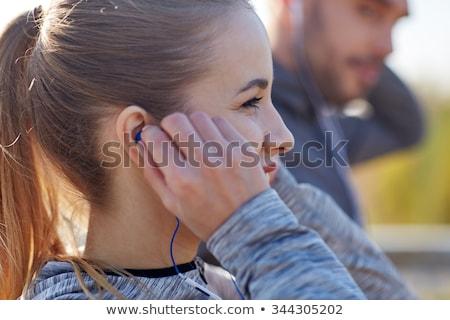 happy couple with earphones running outdoors Stock photo © dolgachov