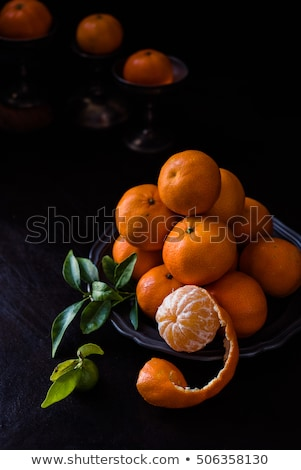 peeled clementine with peel as though a snail coming out of a plate. Chiaroscuro with side light Stock photo © faustalavagna