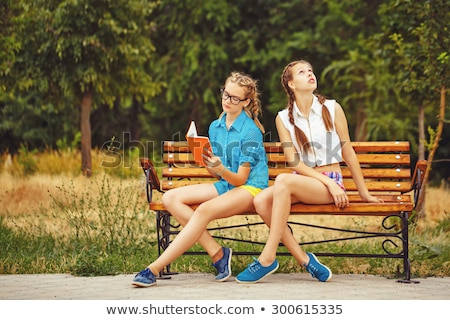 Stockfoto: Hipster With Model Sitting On A Bench In Park