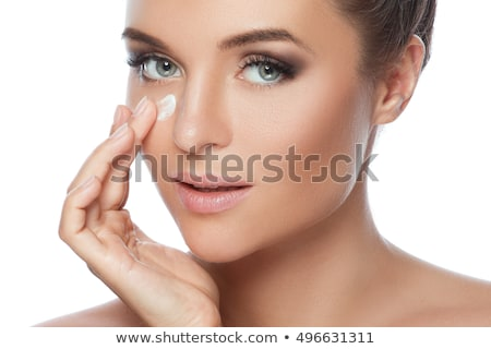 Young woman applying anti-aging moisturizer on her cheeks Stock photo © Kzenon