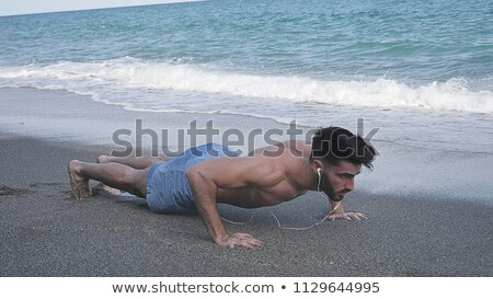 Fiatalember fekvőtámaszok homokos tengerpart tengerpart férfi természet Stock fotó © IS2