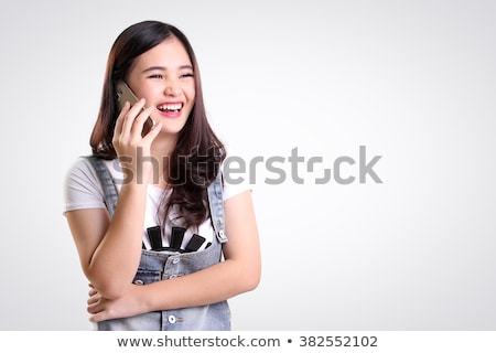 Portrait of a cheerful asian girl talking on mobile phone Stock photo © deandrobot