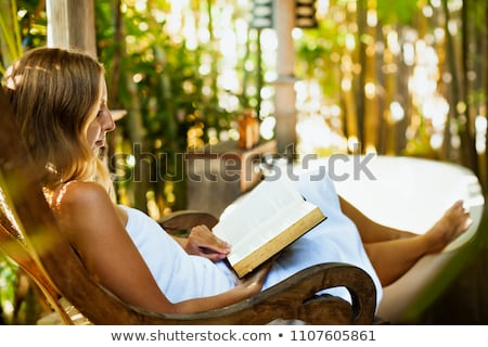 A woman sitting on a rock reading in nature Stock photo © lovleah