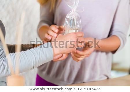 woman giving perfume gift to her friend stock photo © kzenon