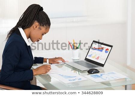 üzletasszony · grafikon · asztal · mosolyog · iroda · számítógép - stock fotó © andreypopov