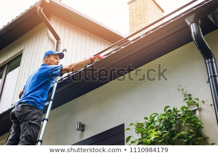 Man on a ladder cleaning house gutters Stock photo © Zerbor