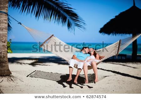 Attractive couple relaxing on a tropical beach Stock photo © konradbak