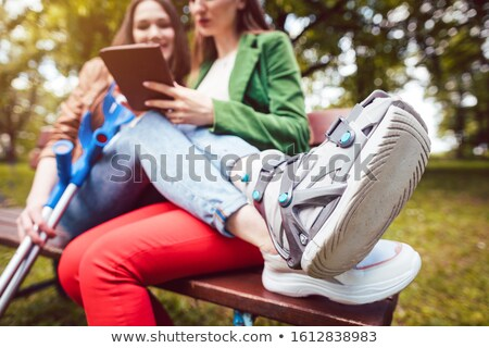Two best friends, one with an injured leg, reading a book Stock photo © Kzenon