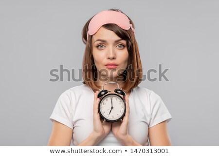 Fiatal barna hajú női ébresztőóra mutat délelőtt Stock fotó © pressmaster