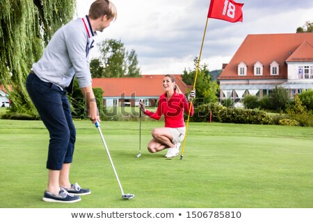 Girlfriend looking at male golfer putting the ball in green Stock photo © Kzenon