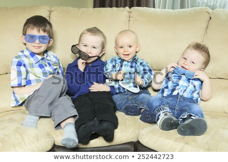 Four little kid site on the sofa Stock photo © Lopolo