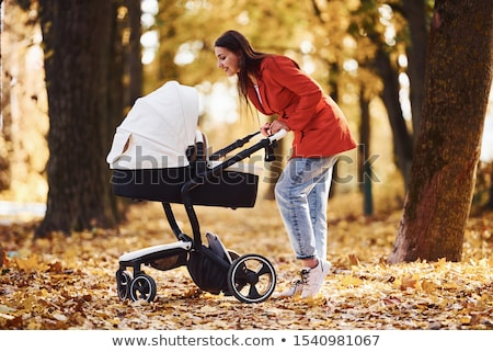Parents Walking with Kid in Baby Carriage, Family Stock photo © robuart