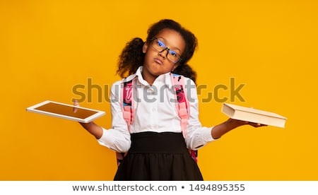 Adorable elementary schoolgirl in eyeglasses reading book in front of camera Stock photo © pressmaster