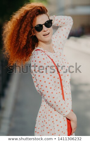 Vertical shot of lovely woman in trendy sunglasses, has curly bushy red hair, carries small bag, pos Stock photo © vkstudio