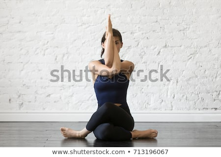 Young woman practicing yoga doing Gomukhasana, cow face pose, in dark room. Stock photo © GVS