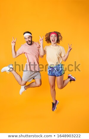 Full length image of athletic happy couple clenching fists in tr Stock photo © deandrobot
